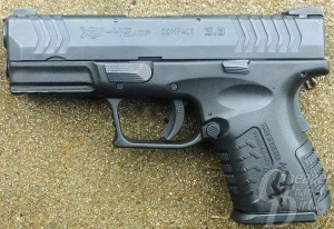 Dark silver/gray Springfield XDM, barrel pointed to the left on a light brown background