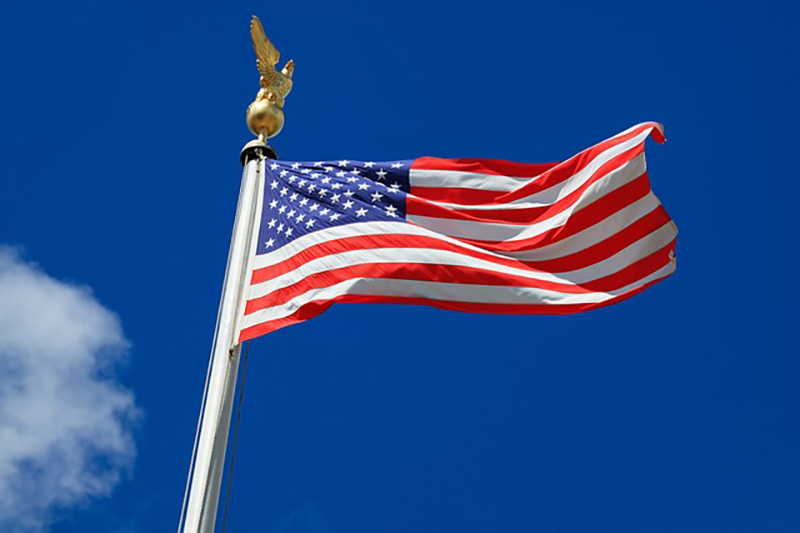 Picture shows the American flag against a bright blue sky
