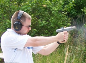 Man in white shirt practicing with a 1911, wooded area in the background