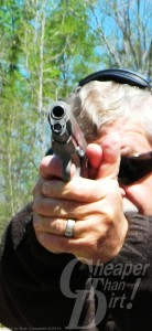 Gray haired man practicing with a 1911