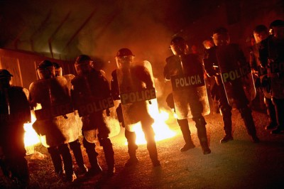 Picture shows a row of SWAT team holding riot shields standing in front of a fire