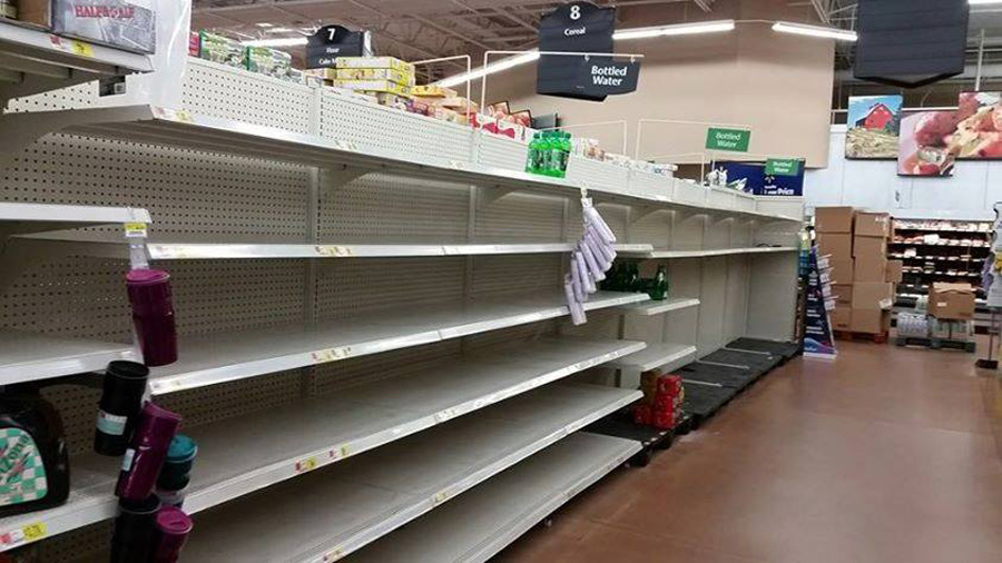 Picture shows shelves empty at a grocery store.
