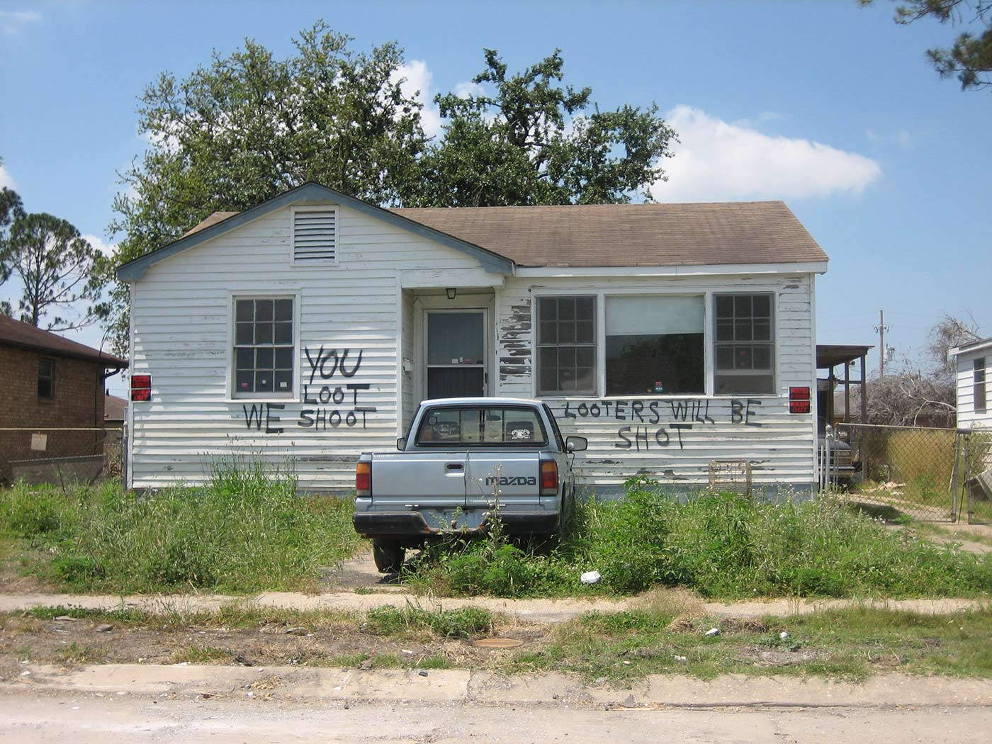 "Picture shows a house in New Orleans sprayed painted with the words, ""You loot, we shoot."""
