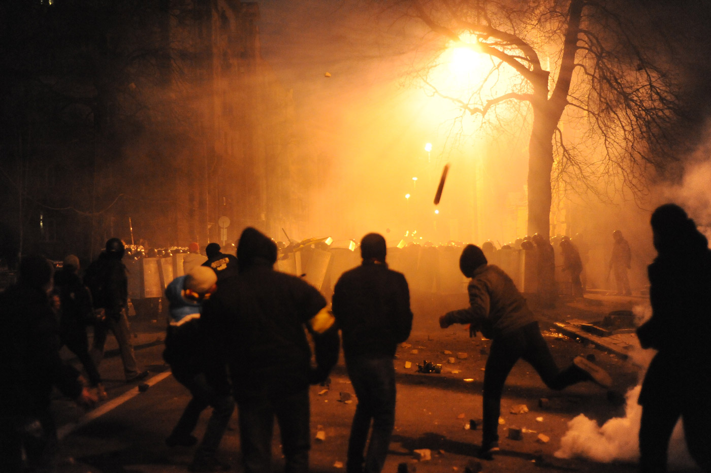 picture shows rioters throwing molotov cocktails on an already burning fire