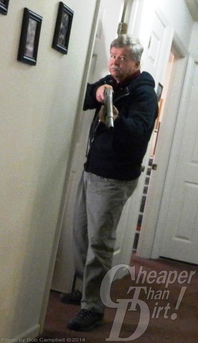 Gray haired man in dark sweater and gray pants holding a shotgun in the hallway of his home.