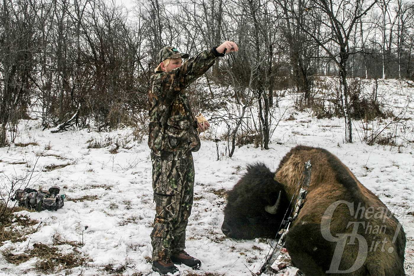 Hunter performing a tobacco ceremony over a downed bison.