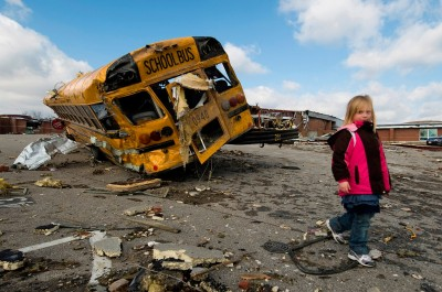 Picture shows a little girl walking in front of a destroyed school bus.