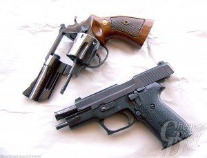 Two revolvers, the top brown handled, barrel pointing down, the bottom a black revolver, barrel pointed down on a white background