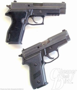SIG P229 on bottom and SIG P227 on top on a barrels to the right white background