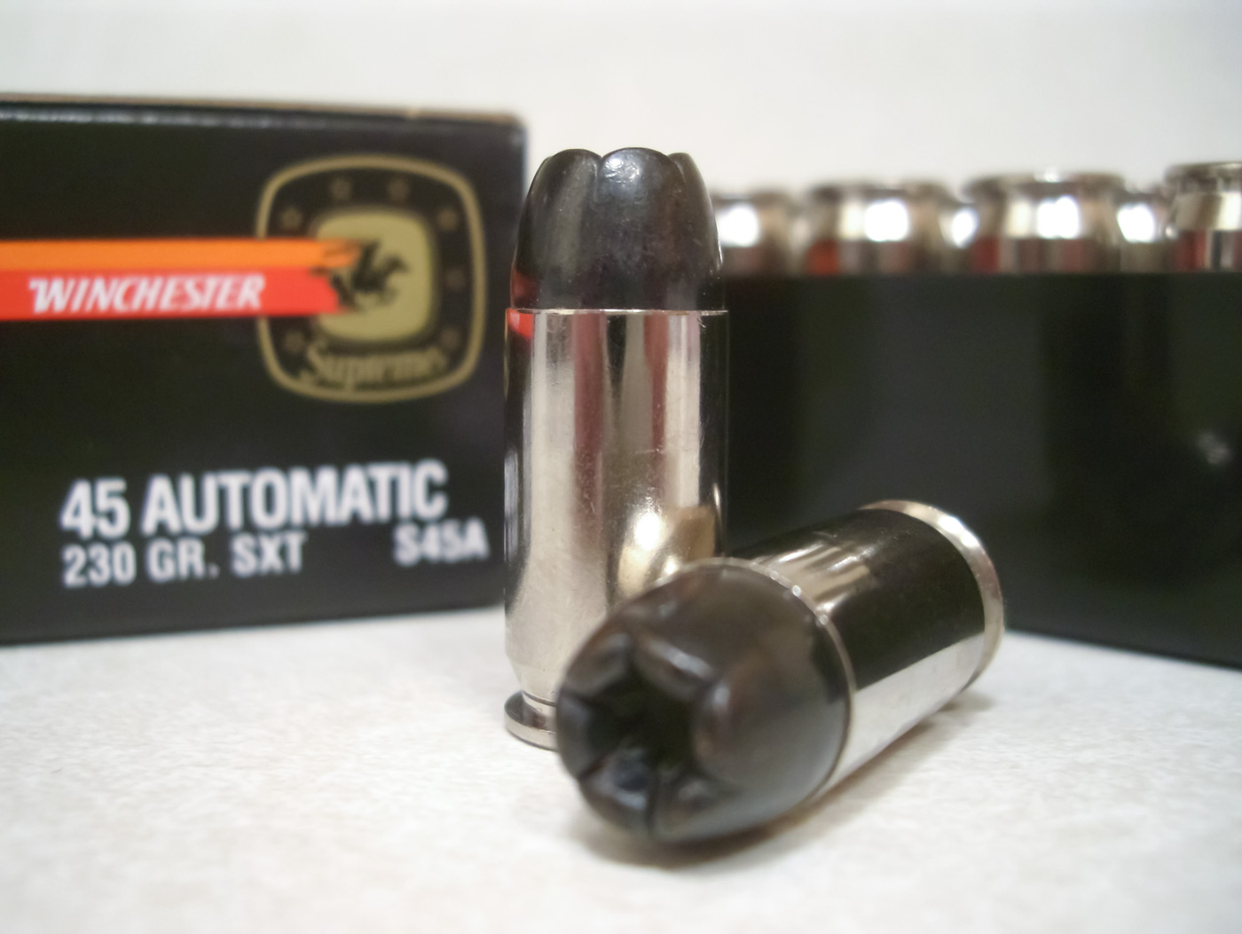 Picture shows a handgun round with shiny case and a black bullet.