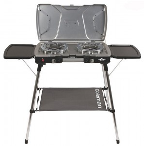 Coleman camping stove with folding side tables, and adjustable telescoping legs