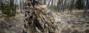 Kryptek camo backback and covered rifle leaning against a tre in a forest