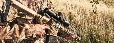 Close up of a Kryptek camo-covered rifle in a grassy field