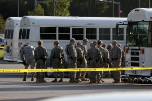 Soldiers standing by white buses