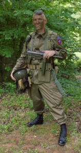WWII reenactor with OD green BDUs and a Grease Gun