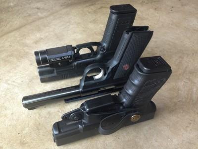 Three pistols highlighting different grip angles