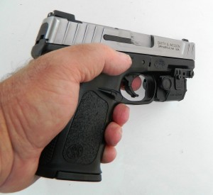 A man holding the S&W SD 40 with attached laser