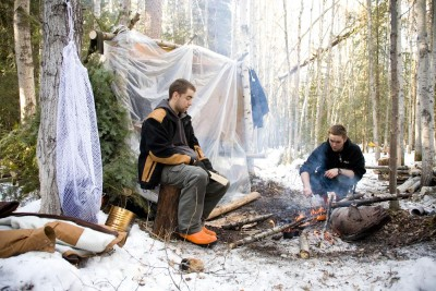 Two men primitive camping in the woods in winter