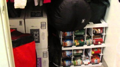 Cans stacked in an organizer in a small coat closet