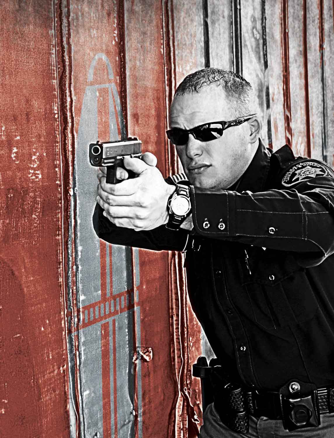 Police Officer aiming a Glock pistol with a red barn in the background
