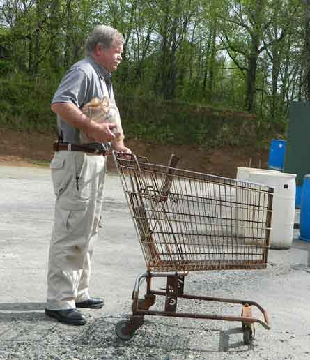 Man pushing shopping cart carrying groceries