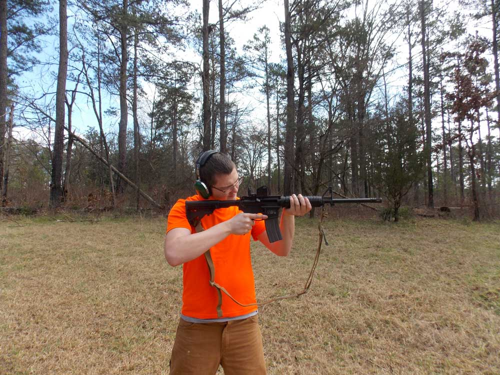 Man with orange shirt shooting AR-15 in field