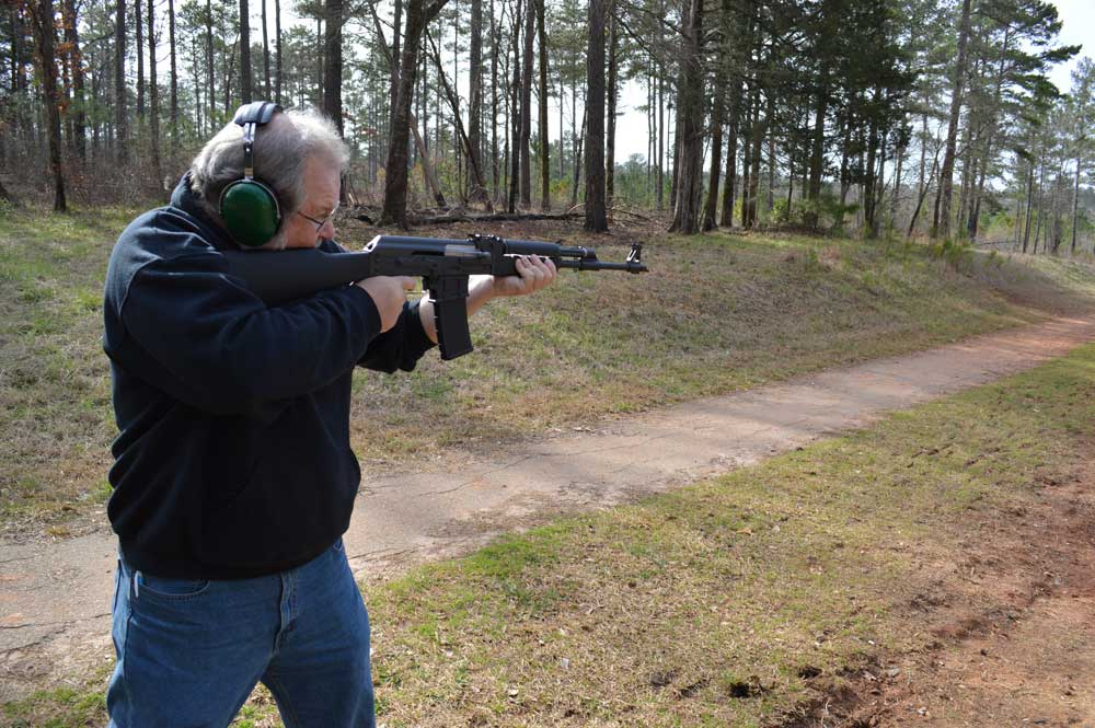 man shooting AK rifle