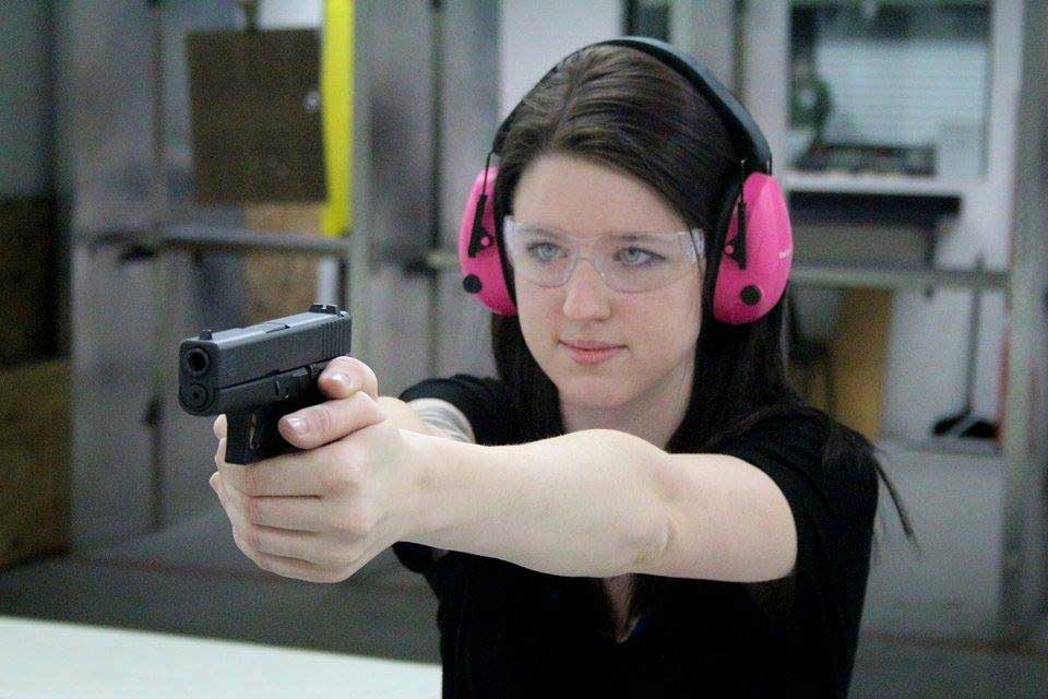 Woman with pink ear muffs shooting a Glock handgun