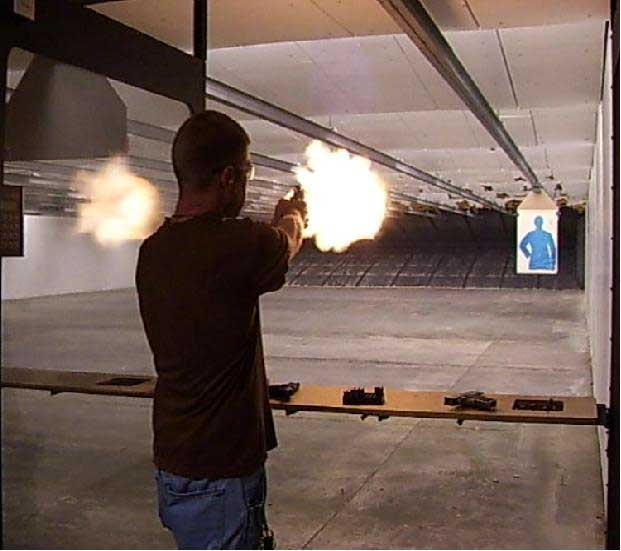 Shooter at indoor range with fiery muzzle blast