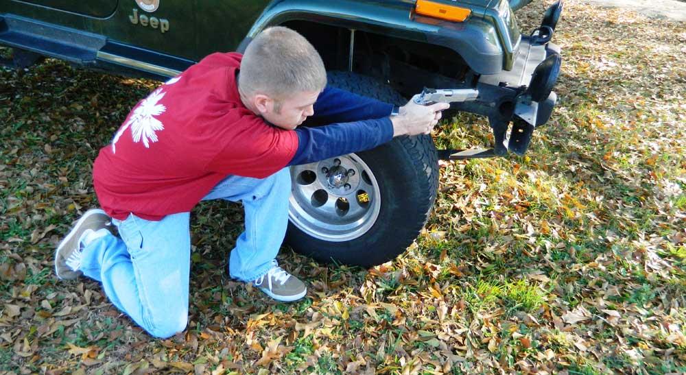 Alan Campbell firing pistol from behind a jeep