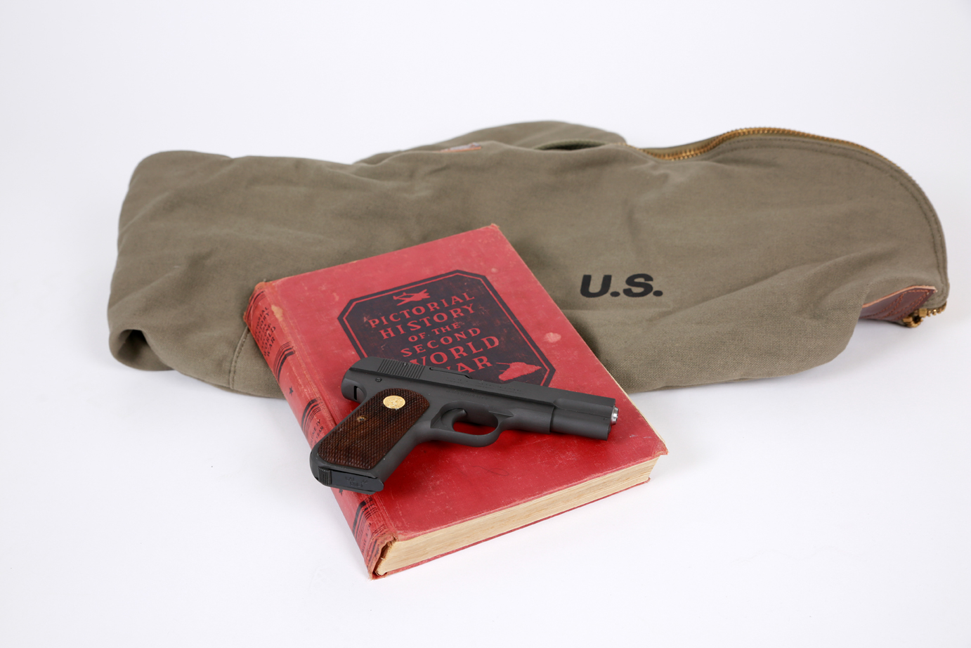 Colt 1903 on OD green bag with red WWII book