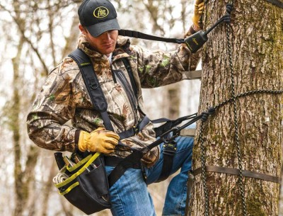 Man in tree wearing HSS Hanger Utility Harness