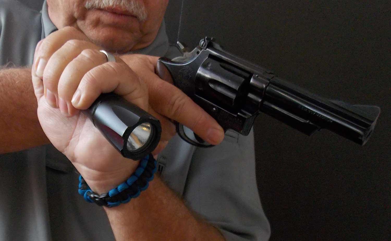 Man holding a revolver and flashlight