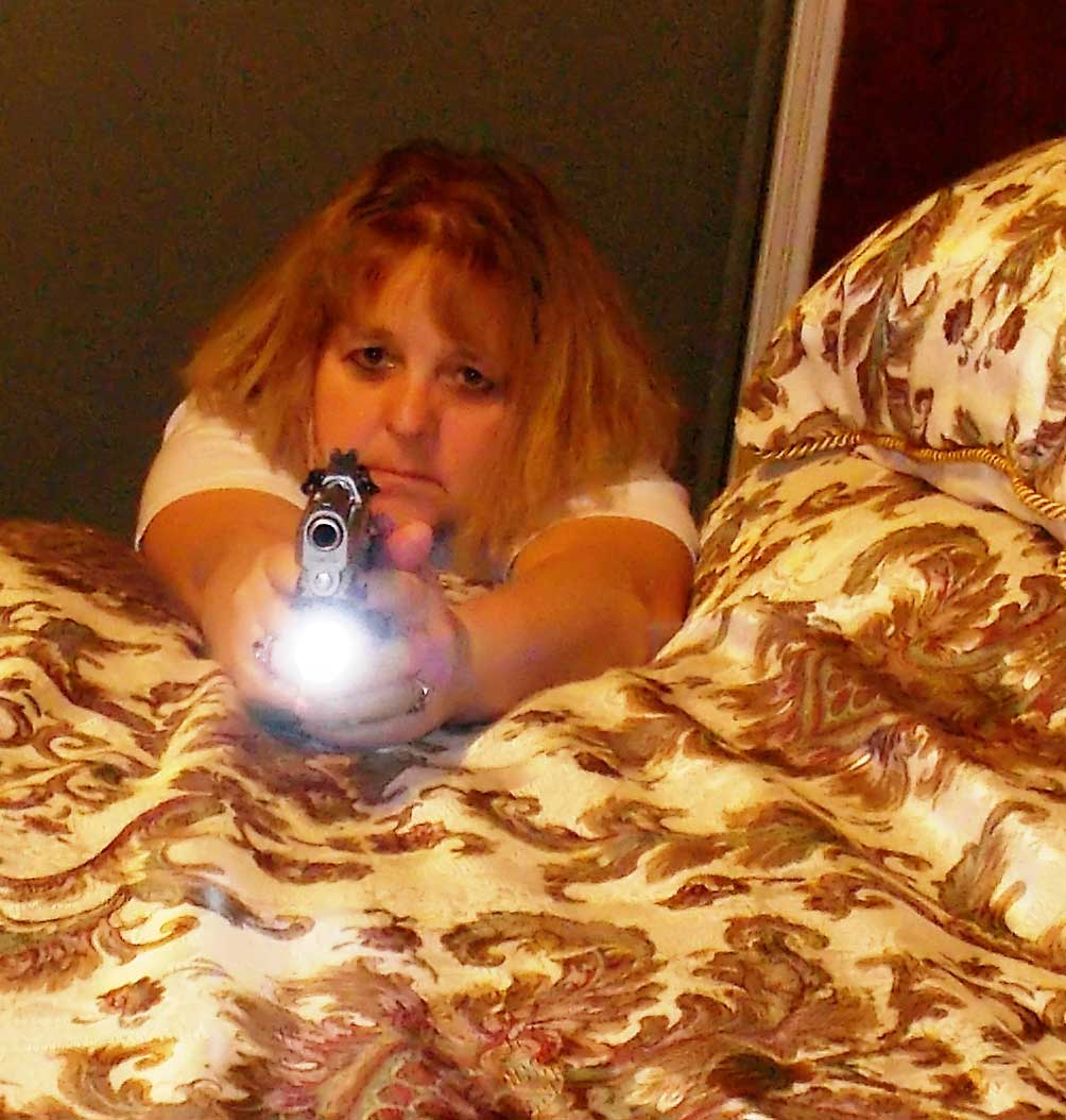 Woman pointing gun over a bed with a light attached and on