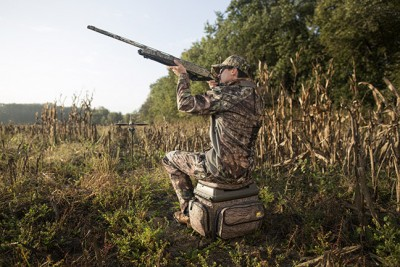 Hunter sitting on Plano 1812 Hunting Stool shooting a shotgun