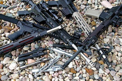 Several AR-15 laying on a bed of rocks