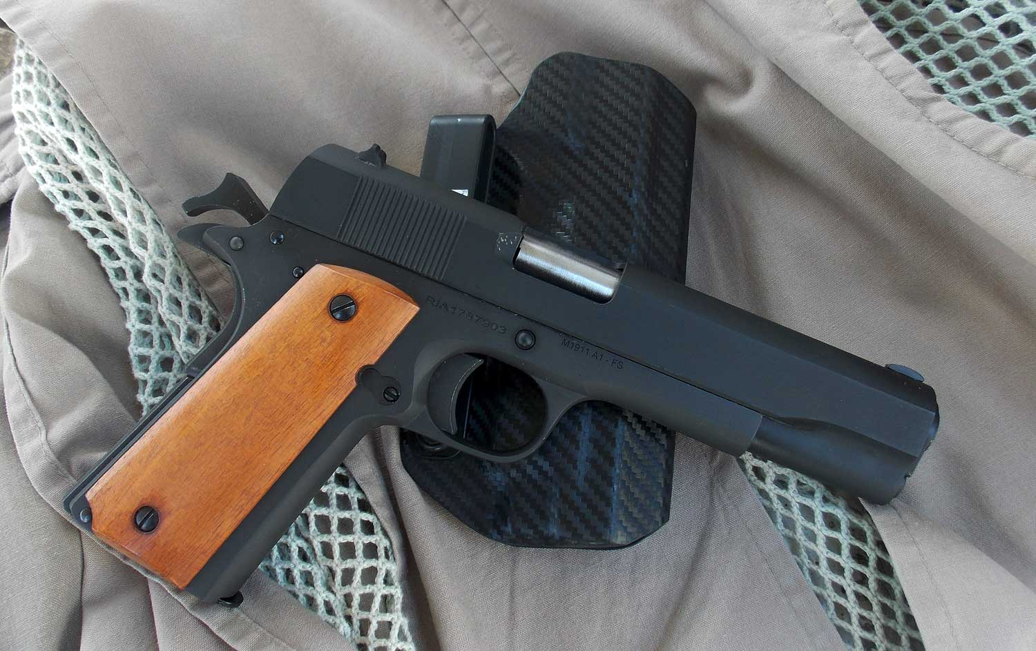 1911 handgun chambered in .38 Super with a Kydex holser