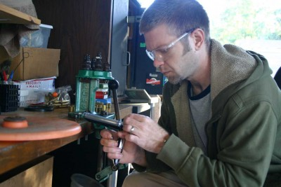 man with reloading press loading ammunition
