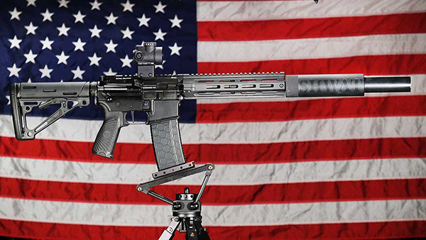 Trijicon MRO atop an AR-15 mounted to tripod in from of the American Flag