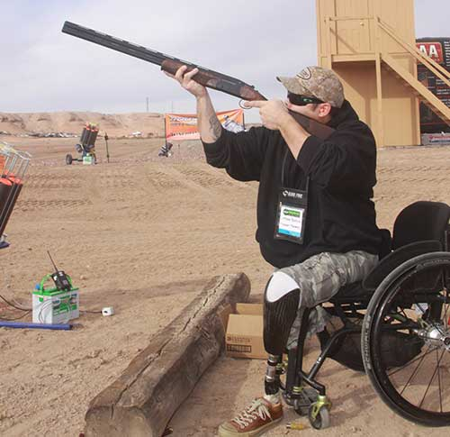 Handicap man shotting a shotgun from a wheelchair
