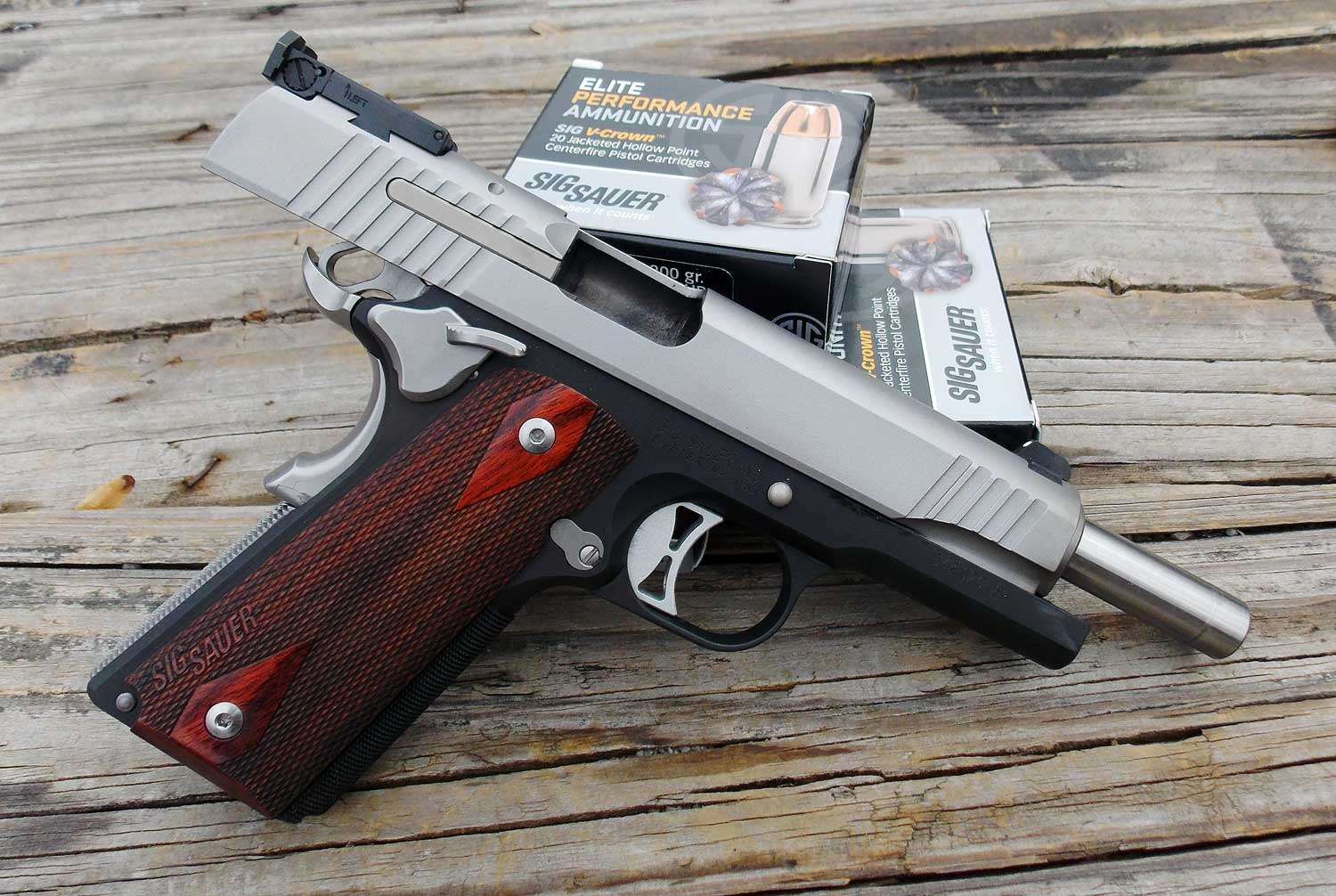 SIG Sauer 1911 pistol with boxes of SIG Elite ammunition