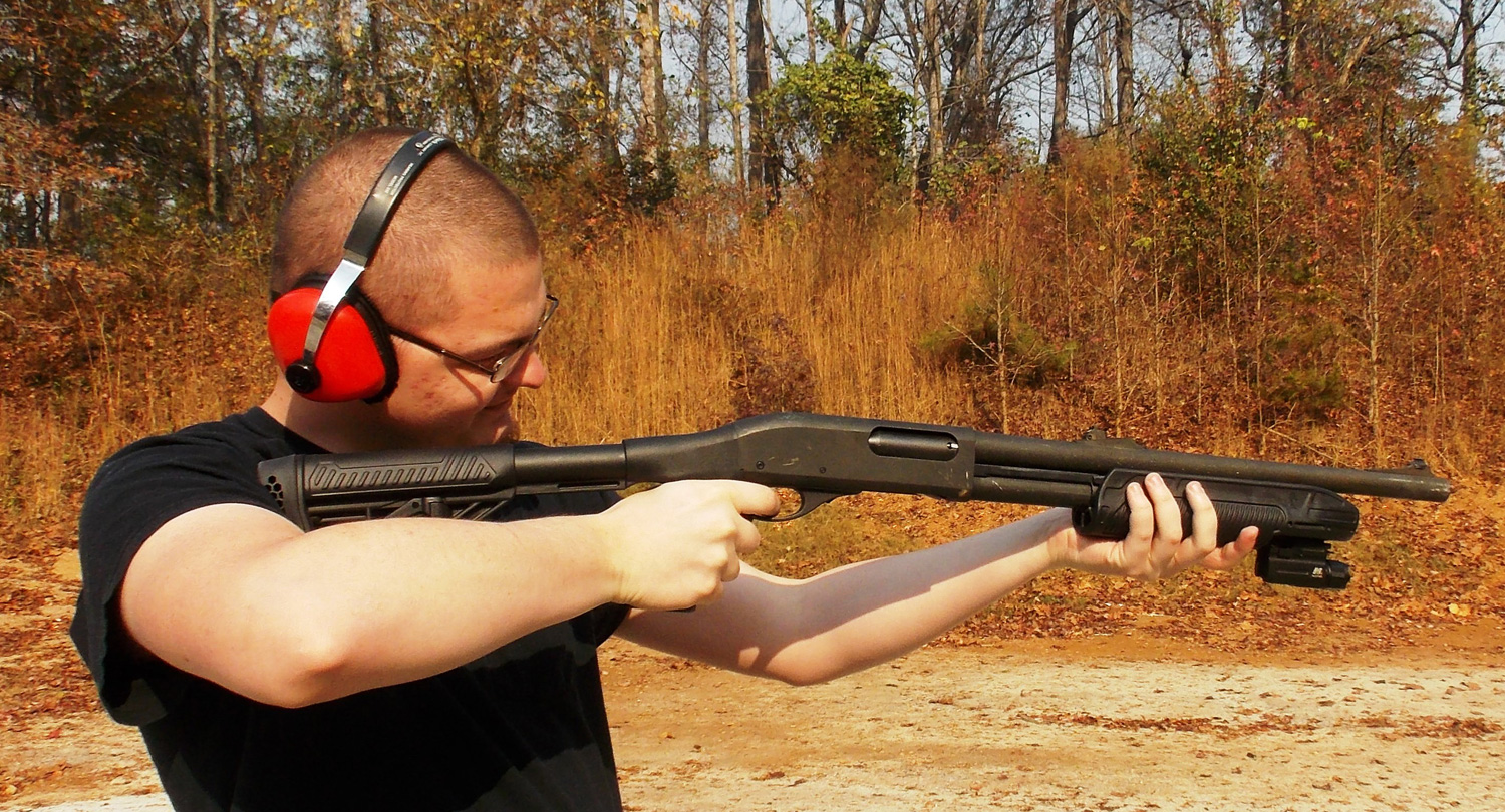 Man holding a Remington 870 shotgun with Adaptive Tactical stock and forend