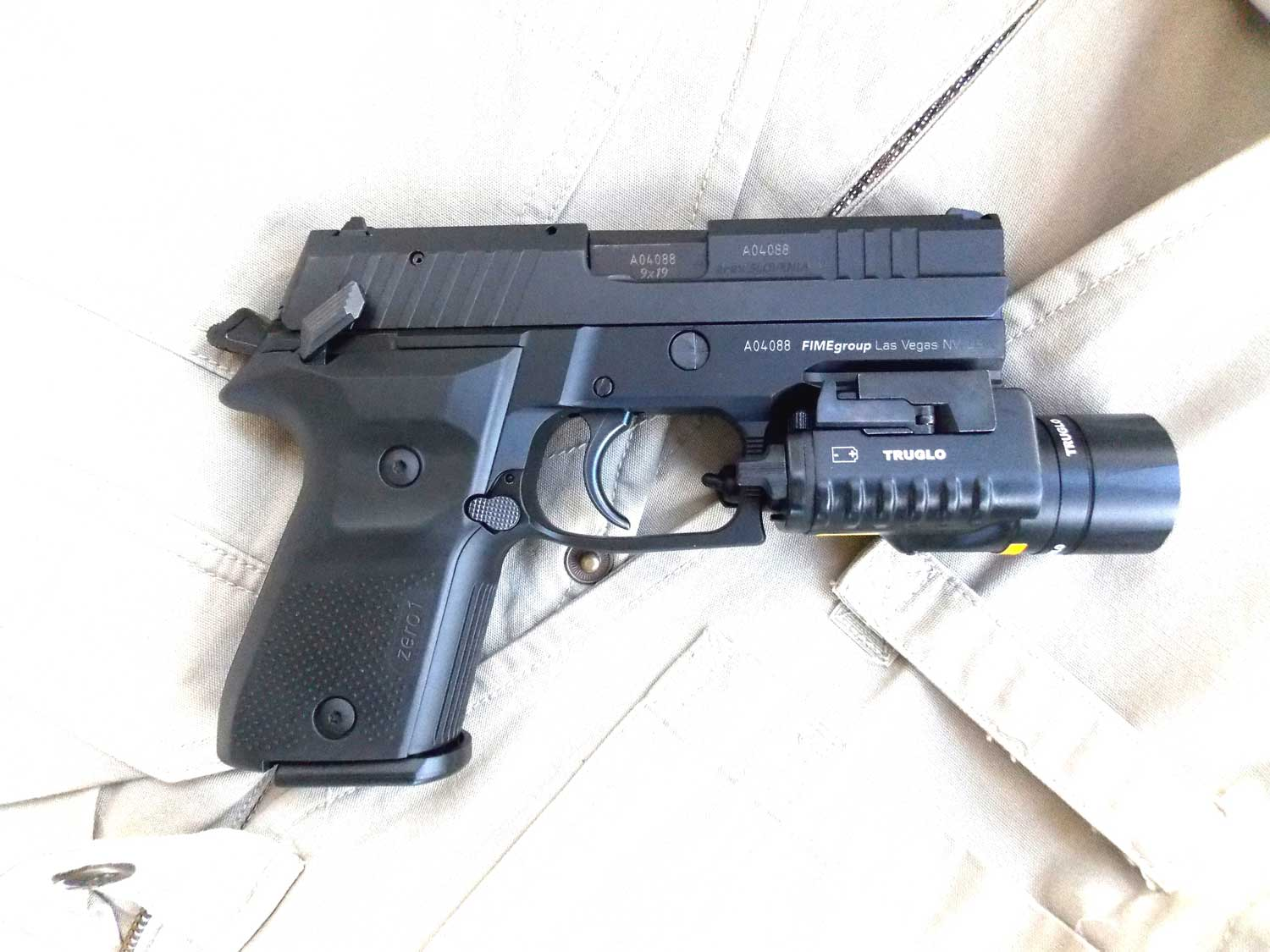 AREX Rex pistol equipped with a TruGlo TruLite combat light right