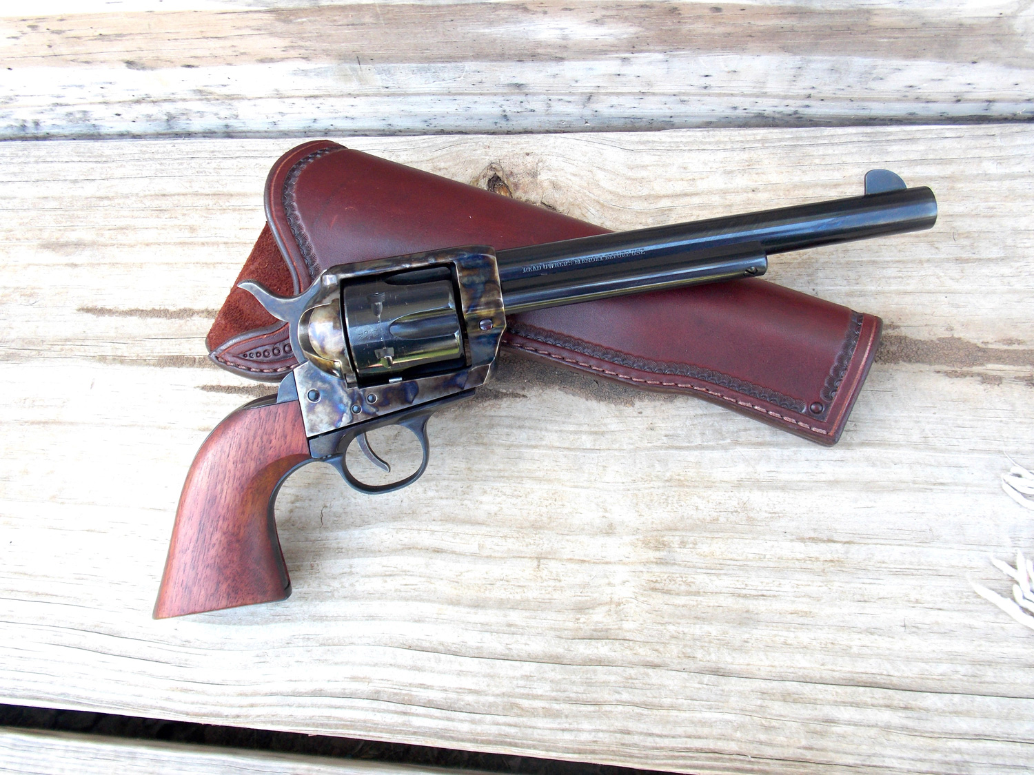 Traditions pistol right lying atop a Custom Bar T holster