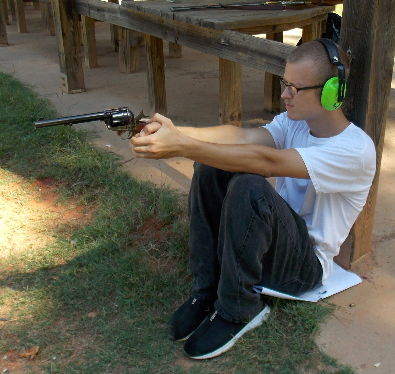 Man in sitting position firing a single action pistol with elbows resting on his knees