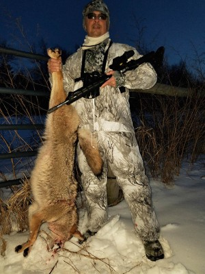 Hunter holding a dead coyote