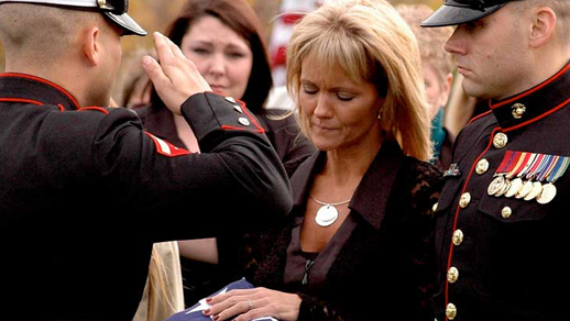 Mother receiving a flag at a military funeral