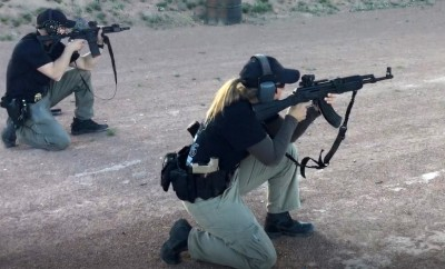 Woman in a crouched position shooting an AK-47