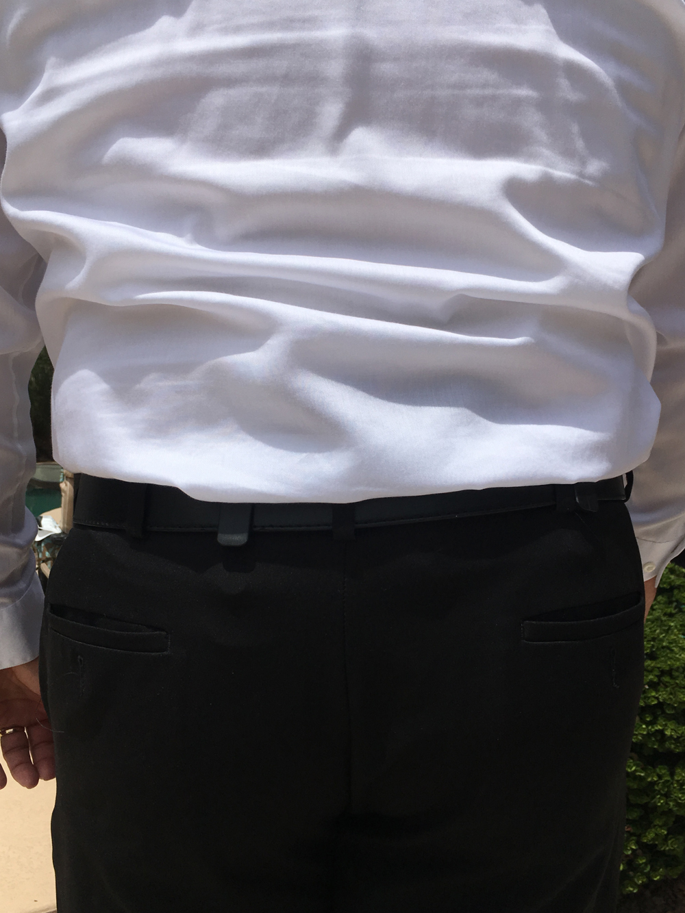Man with concealed firearm wearing a white dress shirt