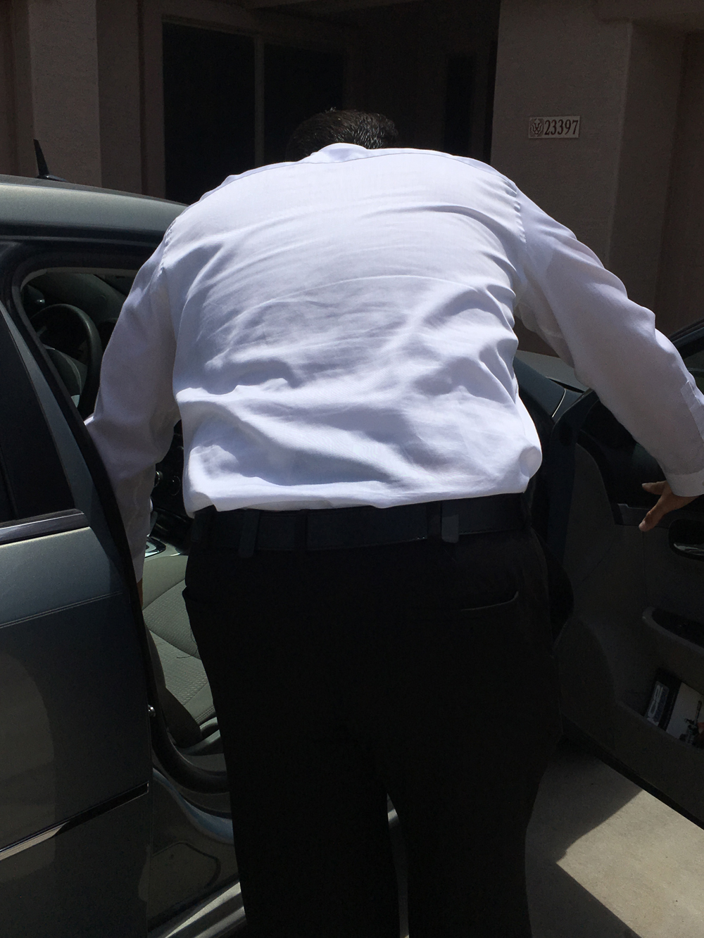 Man wearing a white dress shirt while concealing a pistol